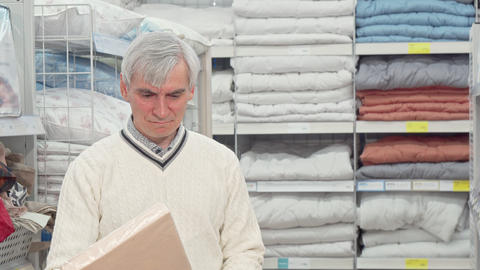 Senior man shopping for bedroom textile at furnishings store Footage