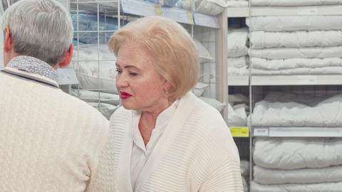Lovely senior lady and her husband choosing linen for their home Live Action