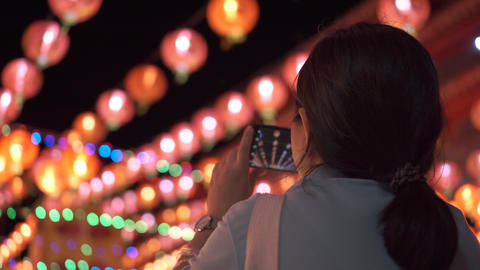 Asian woman take a picture of beautiful lanterns hanging above with smartphone Live Action
