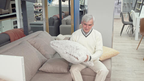 Cheerful elderly man trying soft cushions on sale at furniture store Footage