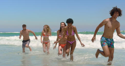 Young friends running together at beach 4k Live Action