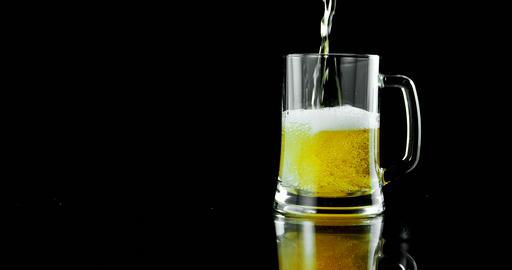 Beer poured in beer mug against black background 4k Live Action