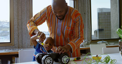 Father and son repairing toy car in a comfortable home 4k Live Action