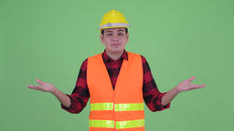 Confused young multi ethnic man construction worker shrugging shoulders Footage