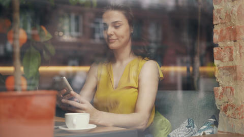 Attractive young lady using smartphone in cafe relaxing with gadget and coffee Live Action