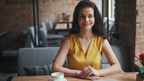 Portrait of attractive girl sitting in cafe with drink looking at camera smiling Footage