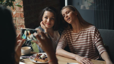 Attractive young women taking photo in diner posing looking at smartphone camera Live Action