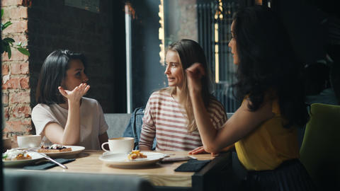 Laughing girls friends putting hands together in cafe enjoying friendship Footage