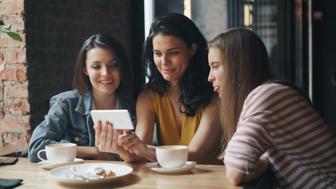 Happy young people watching funny content on smartphone screen in cafe laughing Live Action