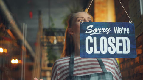 Cheerful waitress changing closed to open sign smiling waiting for customers Footage