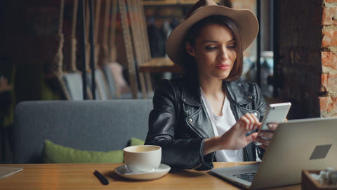Attractive young woman using smartphone in cafe enjoying social media smiling Footage