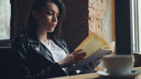 Attractive girl student reading book in cafe relaxing sitting at table alone Footage
