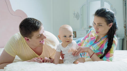 Happy family - mother, father and baby on the bed in the morning Live Action