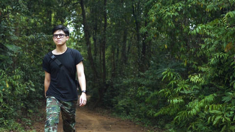 Good looking asian guy wondering around the forest to refresh himself. Good for mental health. Live Action