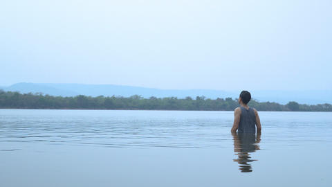 Good looking asian guy standing then swimming at the big lake. refreshing himself with cold water Footage