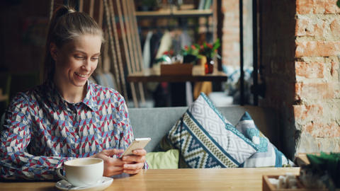 Cheerful girl touching smartphone screen in cafe sending voice message talking Footage