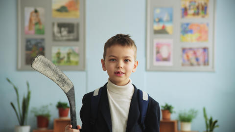 boy without front tooth holds hockey stick in classroom Live Action