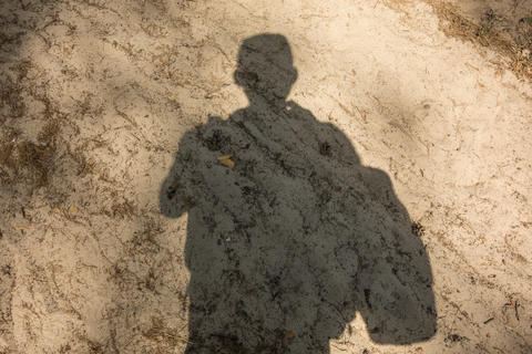 Shadow of man on send track pathway in forest. Concept of active lifestyle, tourism and hiking Fotografía
