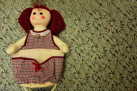 Handmade sew doll with smiling face on floral print background with copy space Fotografía