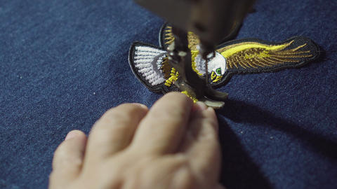 Lady tailor use sewing machine for stitching eagle symbol patch Footage