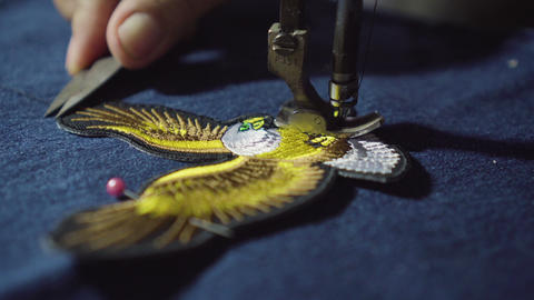 Lady tailor cut a thread from eagle symbol on top of jeans. Prepare for stitch with sewing machine Footage