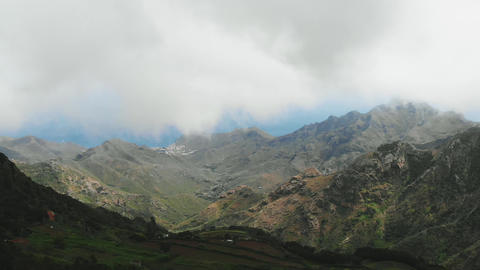 Beautiful aerial panorama of green hills, over which the clouds fly. Tenerife Footage