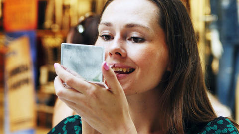 pretty woman in dress paints lips looking in pocket mirror Footage