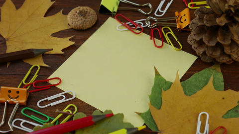 Yellow Sheet of Paper with Yellow Fallen Maple Leaves and Office Supplies Footage