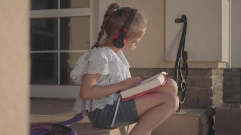 Adorable girl during summer vacation sitting on the courtyard near house Footage
