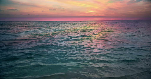 tropical caribbean beach sea with gold sand and rocks at sunset, colorful of sky with slow sea Live Action