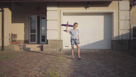 Adorable little girl playing with the small toy plane close-up. The girl Footage