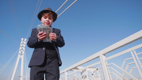 Carefree young boy throwing money cash from bridge low angle view. Young boy Live Action