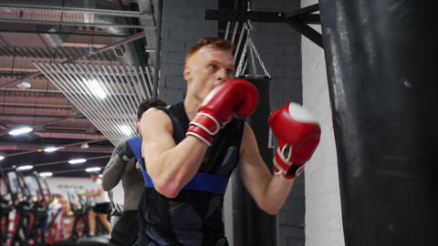Boxer man training punches by boxing bag together personal training in gym club Live Action