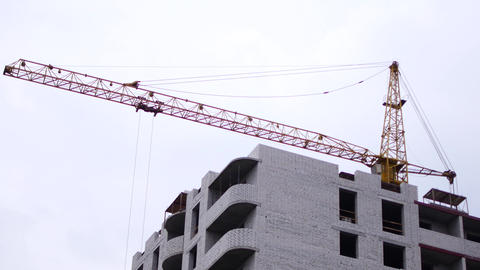 Construction of a multistory, brick building. A mounting crane lifts building Live Action