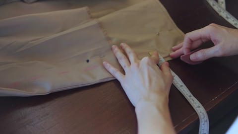 Seamstress marks a pattern on beige fabric Footage