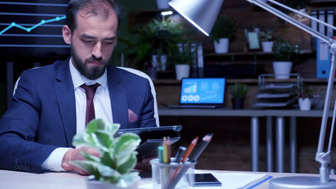 Manager late at night in the office uses a digital tablet PC pad Footage
