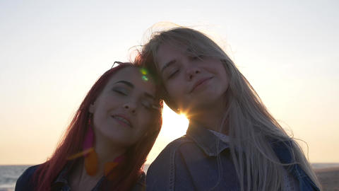 Couple of young women head to head in enjoy the sunset Wind blows hairs at the Footage