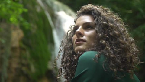 Face of beautiful Young woman with curly hair in green dress in backdrop of Footage