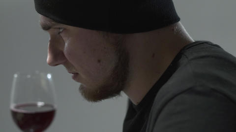 Side portrait of a bearded guy sniffing wine in a wine glass. Leisure of young Footage