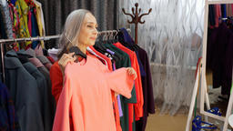 Senior elegant woman is trying pink dress in clothes store Footage