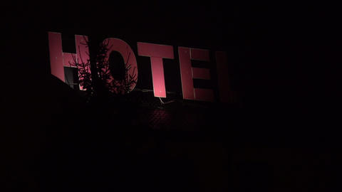 Flickering spooky red hotel sign at night Footage
