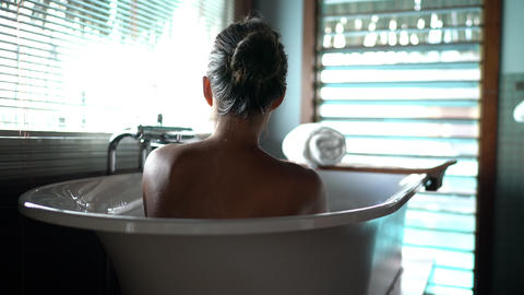 Luxury bath woman relaxing in hot bathtub in hotel resort suite room pampering Live Action