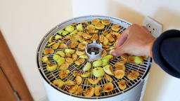 One hand opening lid of dehydrator with sliced cut apple slices in kitchen Footage