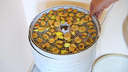 One hand closeup stacking trays of dehydrator with sliced cut apple slices Footage