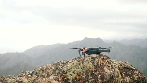 Close up of a consumer drone launching and taking flight off from a rough rock Live Action
