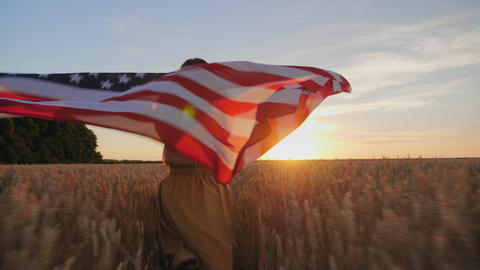 Woman runs with the flag of America in the field Footage