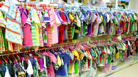 Interior of kids store. Racks with kids clothes and shoe display wall shelves in children's clothing Footage