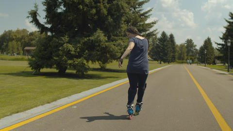 Skillful female rollerblading backwards outdoors Live Action