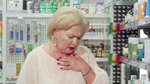 Elderly woman feeling sick, looking for medicine at local pharmacy Live Action