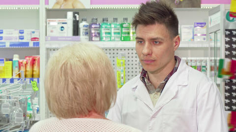 Young male pharmacist talking to his elderly client Live Action